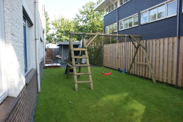 ... tuinhuisje schutting beplanting gazon trampoline schommel glijbaan